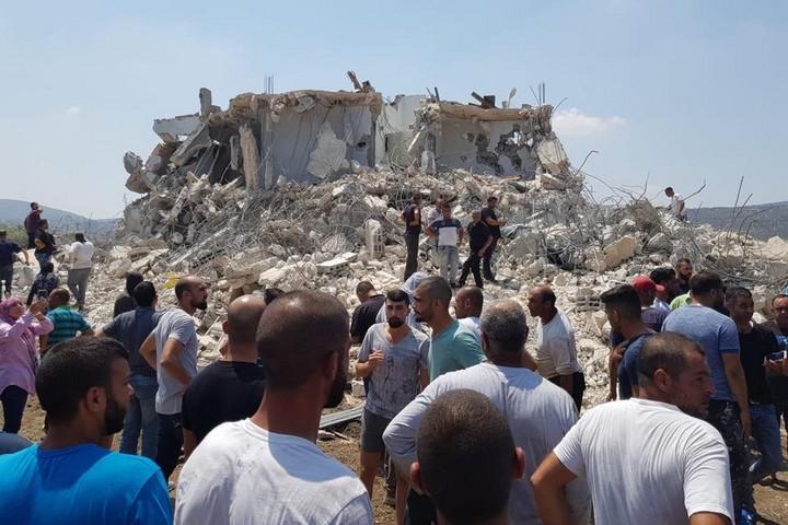 """תושבים על רקע הבית ההרוס בסכנין. (צילום: עומר דלאשה, אתר """"ערב48"""")"""