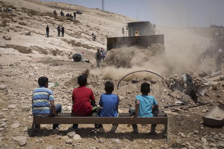 ילדים מול בולדוזר בח'אן אל אחמר. עכשיו המדינה מצפה שהם ישכנעו את שכניהם הבודאים מעבר לכביש להתפנות (צילום: אורן זיו / אקטיבסטילס)
