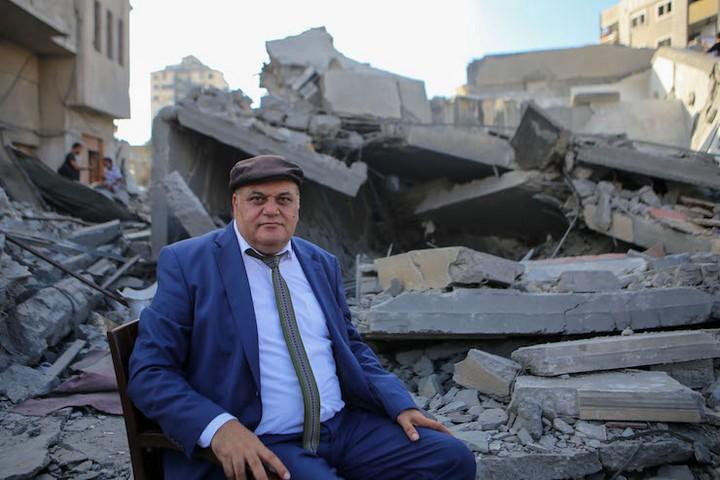 מנהל מרכז אל-משעל עלי אבו יאסין על רקע ההריסות. שימש בית לאמנים בעזה (צילום: מוחמד חג'אר)