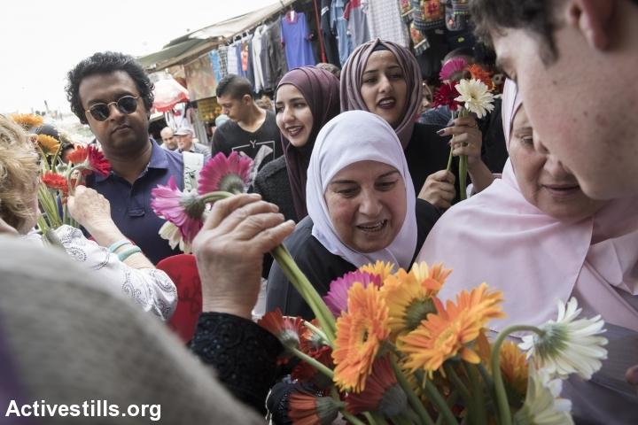 """פעילי """"תג מאיר"""" מחלקים פרחים לפלסטינים במהלך """"מצעד הדגלים"""" ביום ירושלים. 14 במאי 2018, ירושלים העתיקה. (אורן זיו / אקטיבסטילס)"""