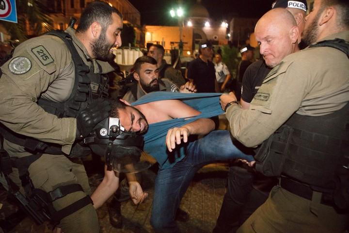 עצור בהפגנה בחיפה נגד הרג המפגינים בעזה. חמש שנים מתוחות ביחסי יהודים וערבים (צילום: נדין נאשף)