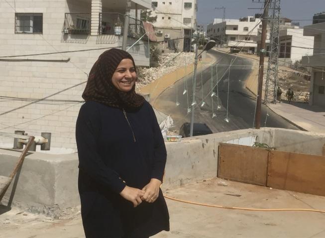 סוזאן ג'אבר על גג ביתה. ברקע ניתן לראות את הרחוב הראשי בשכונת ג'אבר הריק ממכוניות פלסטיניות (רמי יונס)