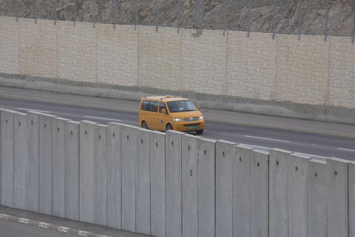 מונית פלסטינית בקטע הכביש בו יש חומות משני הצדדים (אורן זיו / אקטיבסטילס)