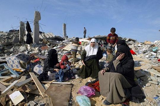 משפחה עזתית על חורבות ביתם ושכונתם שנחרבו בעופרת יצוקה, ינואר 2009 (עבד רחים ח'טיב/ פלאש 90)