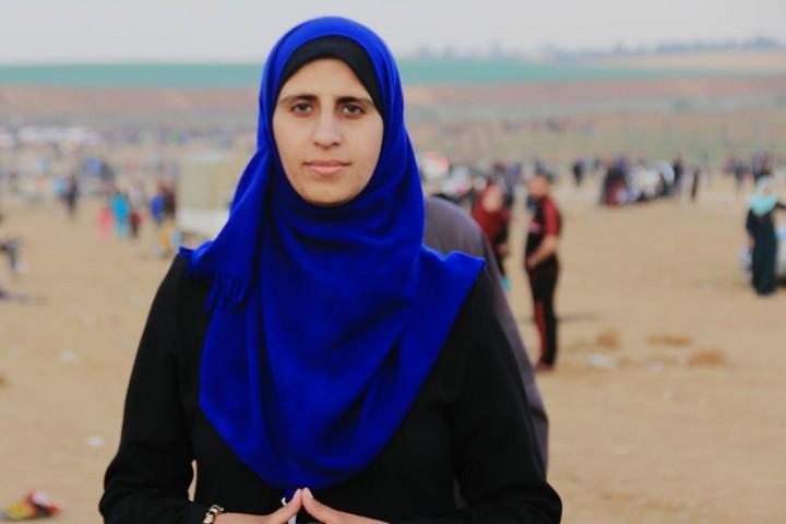 מסקרת את ההפגנות, אבל המבט לעבר כפר שבו נולדה משפחתה. אסרה אע'יר ליד הגדר בעזה (צילום: סלסביל חמדאן)