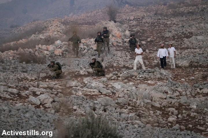 החיילים התרגלו לפעול תחת פיקוד המתנחלים. מתנחלים וחיילים ליד הכפר בורין (צילום: אחמד אל באז / אקטיבסטילס)