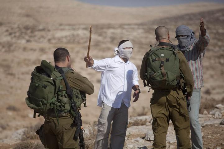 """הרבש""""צ אומר, החיילים מבצעים. מתנחלים וחיילים בדרום הר חברון (אורן זיו / אקטיבסטילס)"""