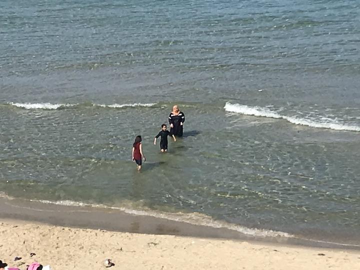 אשה רוחצת עם ילדיה בחוף הים בעזה (צילום: ג'ן מרלו)
