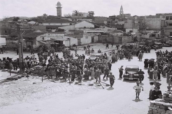 """השלט מספר שתושבי אבו כביר """"עזבו"""" במהלך הקרבות ב-1948. הוא לא מספר שגם התושבים בשכונות היהודיות הקרובות ברחו. מחסום בריטי במרכז אבו כביר ב-1947 (צילום: באדיבות אתר יאפא 48)"""