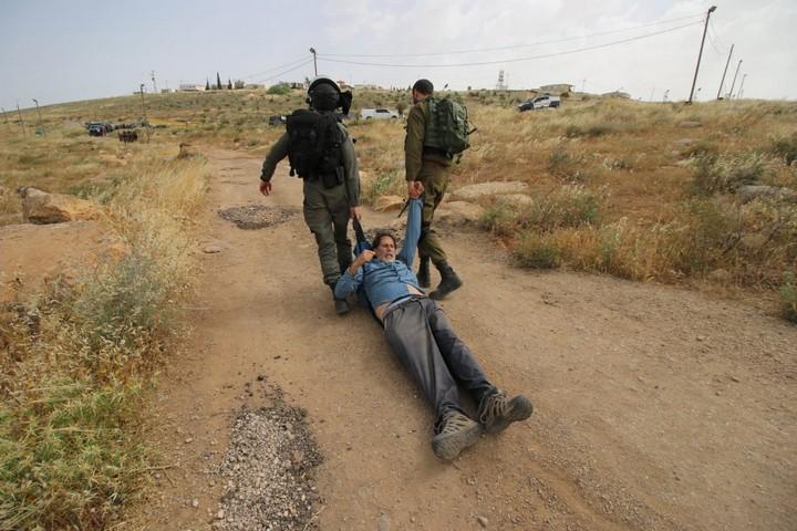 """פעיל השמאל אריק אשרמן נגרר על הארץ בידי חיילים. הצילום ש""""עלה"""" לאלבאז במעצר (צילום: אחד אלבאז / אקטיבסטילס)"""