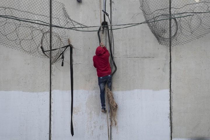 מהצד השני של החומה, הם השתלשלו בחבל, מהר לפני שהשוטרים יגיעו. (צילום: אורן זיו / אקטיבסטילס)
