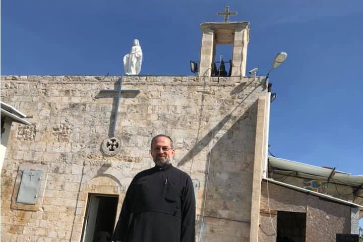התחילו עם הלוויות בבית הקברות של הכפר ההרוס, עכשיו עברו לחתונות. הכומר סוהיל ח'ורי על רקע הכנסייה באיקרית (צילום באדיבות דף הפייסבוק איקרית)