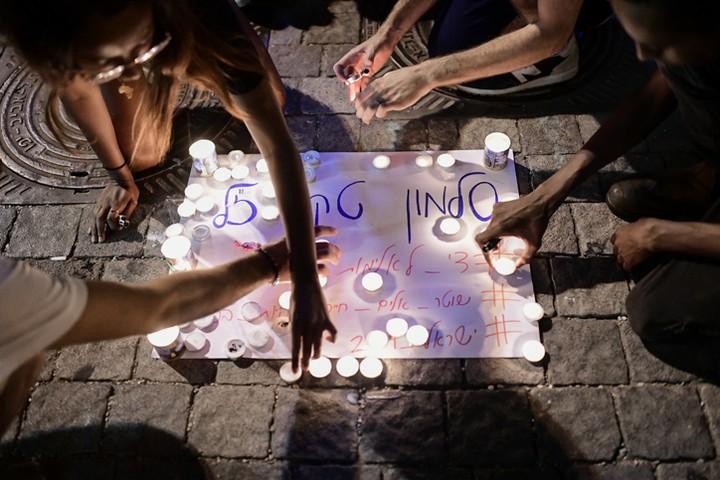 צעירים מדליקים נרות לזכרו של סלומון טקה. 2 ביולי 2019 (תומר ניוברג / פלאש 90)