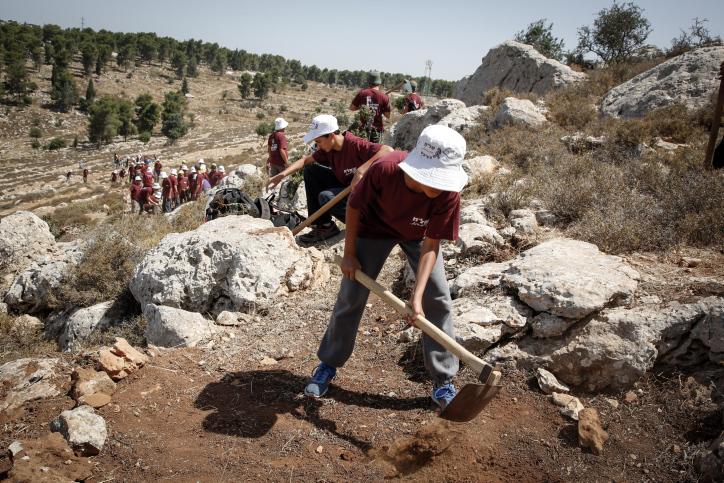 בטיול לגוש עציון, המדריך מנשק את רגבי הארץ ואומר: זו אדמה קדושה. תלמידים בגוש עציון. למצולמים אין קשר לכתבה (צילום: גרשון אלינסון)