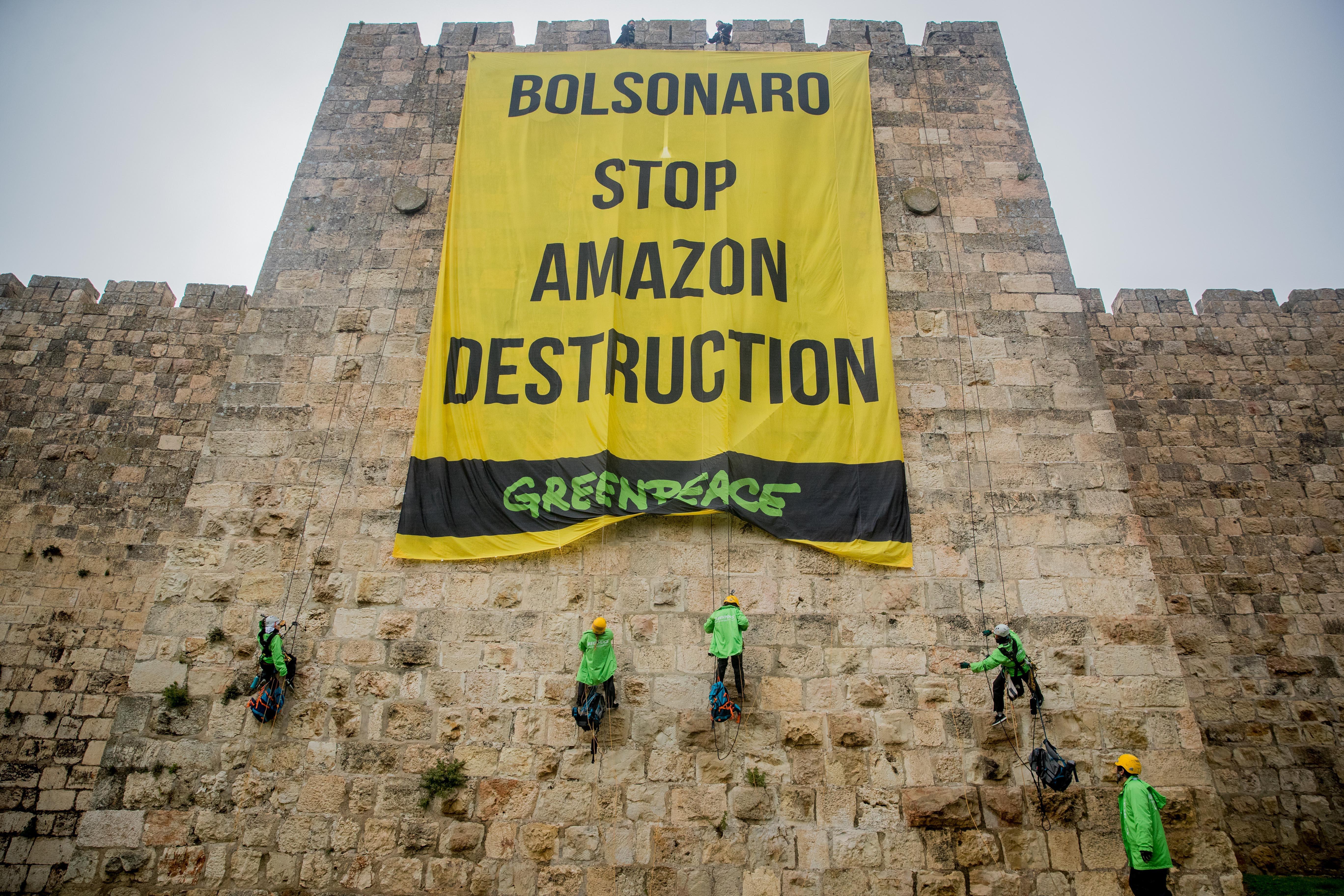"""""""בולסונרו, תעצור את הרס האמזונס"""": מחאה של פעילי גרינפיס בירושלים בזמן ביקורו של נשיא ברזיל ז'איר בולסונרו בישראל, באפריל 2019 (צילום: יונתן סינדל/פלאש90)"""
