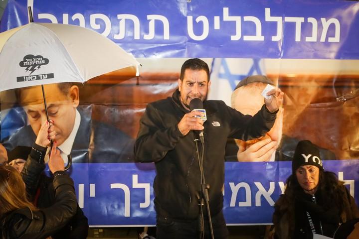 """מני נפתלי מדבר בהפגנה השבועית נגד השחיתות הממשלתית מול ביתו של היועמ""""ש בפתח תקוה, ב-27 בינואר 2018 (צילום: רועי אלימה / פלאש90)"""