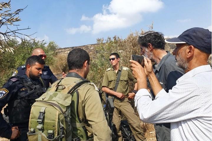 """""""אם הפעילים היהודים לא היו באים, היו מדברים איתנו עם גז מדמיע"""", אמרו הפלסטינים. חיילים מונעים מאנשי רבנים לזכויות אדם להמשיך בקטיף בכפר בורין (צילום: אורלי נוי)"""