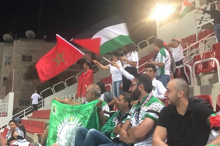 כשהמרוקאים הבקיעו גול, גם האוהדים הפלסטינים קפצו ביציע. אוהדים מניפים דגלי מרוקו ופלסטין ביציע במשחק בין רג'אא קזבלנקה להילאל אלקודס (צילום: סמאח סלאימה)