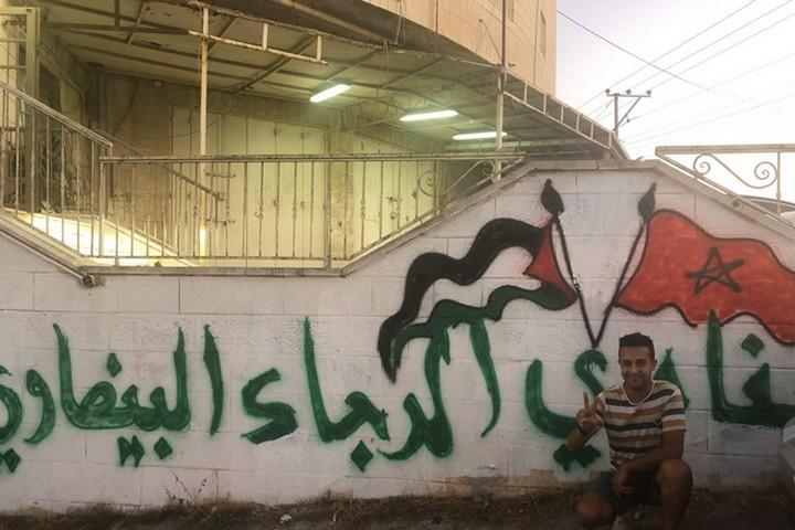 שירי האהבה לפלסטין שכנעו אותי להגיע למשחק. כתובת קיר המשלבת בין דגלי מרוקו ופלסטין מוץ לאיצטדיון בא-ראם (צילום: סמאח סליאמה)