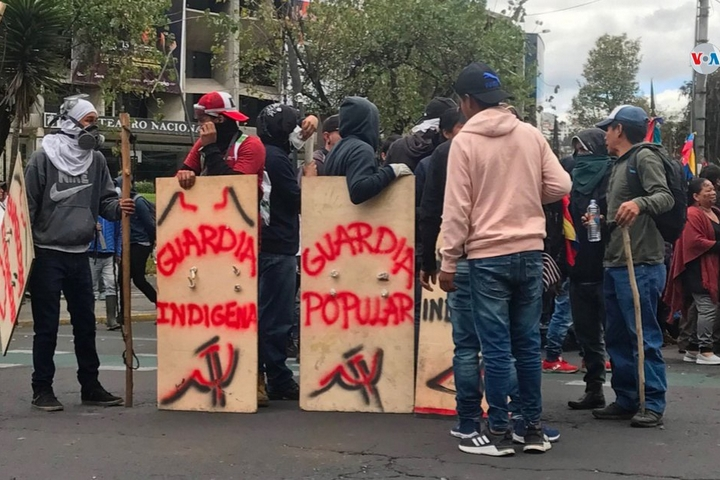 """מחאה באקוודור נגד צעדי הצנע של הנשיא לנין מורנו, נושאים מגיני עץ שעליהם כתוב """"המשמר הפופולרי"""" ו""""המשמר הילידי"""", ב-11 באוקטובר 2019 (צילום: Voz de América)"""
