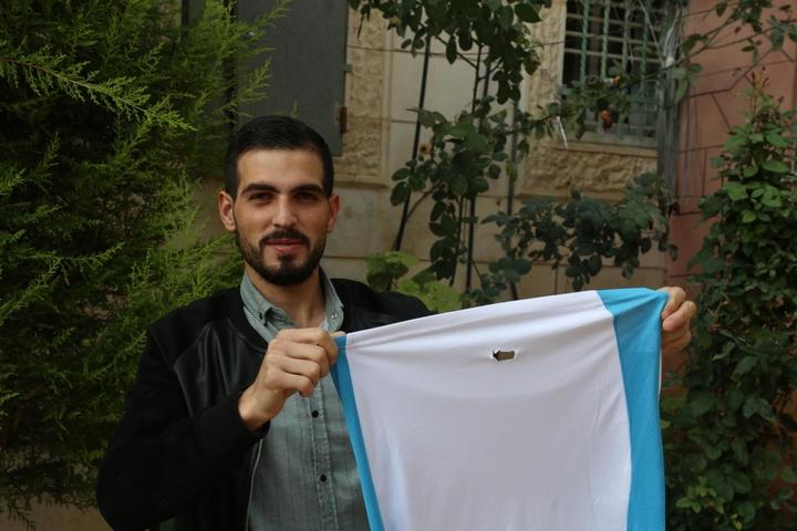 כראם קאוואסמי, פלסטיני בן 22 מחברון, מחזיק את החולצה שלבש כשחייל ישראלי ירה בו בגבו בכדור ספוג (צילום: MEE/Alaa Daraghmeh)