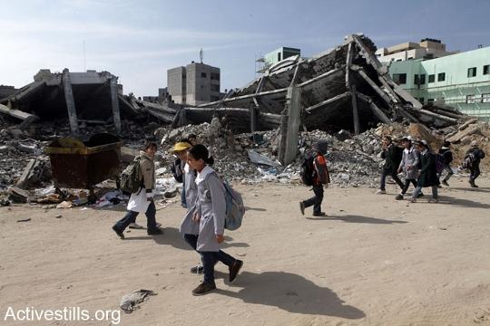 ילדים חולפים על פני חורבות משרד הפנים בעזה, אחרי הפצצה של חיל האוויר, 2013 (אקטיבסטילס)