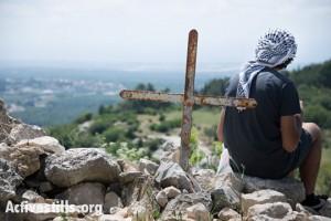 צעיר מביט אל אזור הכפר הפלסטיני המגורש, איקרית, צפון ישראל, ה-21 לאפריל, 2014. (ריאן רודריק ביילר/אקטיבסטילס)