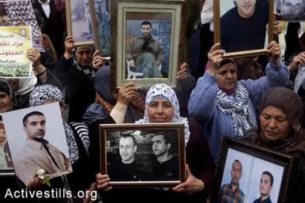 נשים פלסטיניות מציגות תמונות של קרוביהן - אסירים הכלואים בבתי כלא ישראליים. יום האסיר הפלסטיני, רמאללה, ה-17 באפריל, 2014 (אקטיבסטילס)