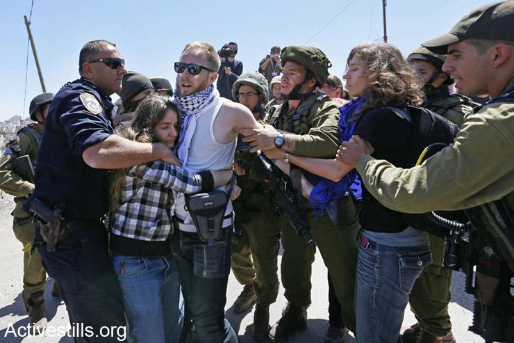 """חיילים ושוטרים ישראלים עוצרים פעילים במהלך הפגנה נגד החלטת ממשלת ישראל לאפשר למתנחלים להכנס ל""""בית ראג'בי"""" בחברון, ה- 11 לאפריל, 2014."""