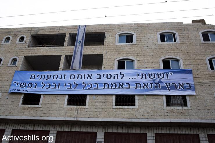 באנר ודגל ישראל תלויים מחוץ לבית, לאחר כניסת המתנחלים לתוכו. ה- 13 לאפריל, 2014.