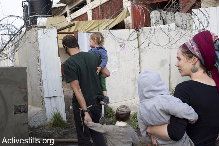 משפחת מתנחלים נכנסת לבית. חברון, ה- 13 לאפריל, 2014.