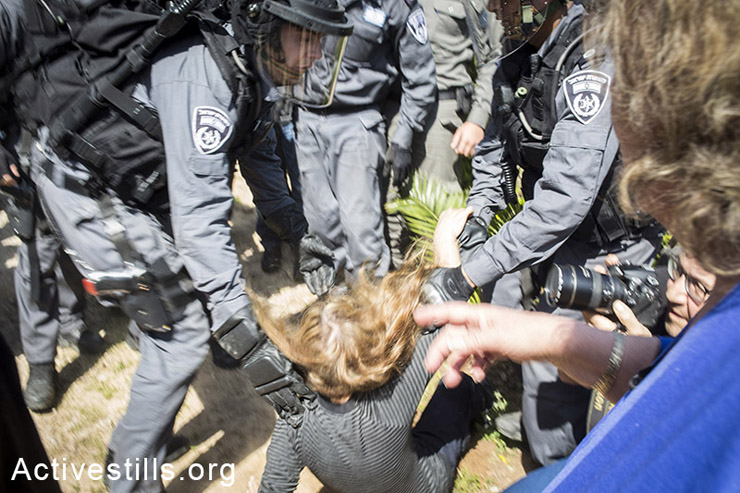 שוטרים דוחפים לקרקע מפגינה בזמן פינוי בשכונת גבעת עמל. המפגינים קראו סיסמאות ושרפו צמיגים. (צילום:קרן מנור/אקטיבסטילס)