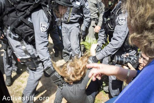 שוטרים דוחפים לקרקע מפגינה בזמן הפינוי בשכונת גבעת עמל. המפגינים קראו סיסמאות ושרפו צמיגים. (צילום:קרן מנור/אקטיבסטילס)
