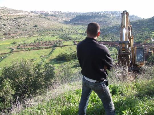 איש ביטחון מפקח על עבודות הזזת הגדר בוואד א-רשא, 2009 (חגי מטר)