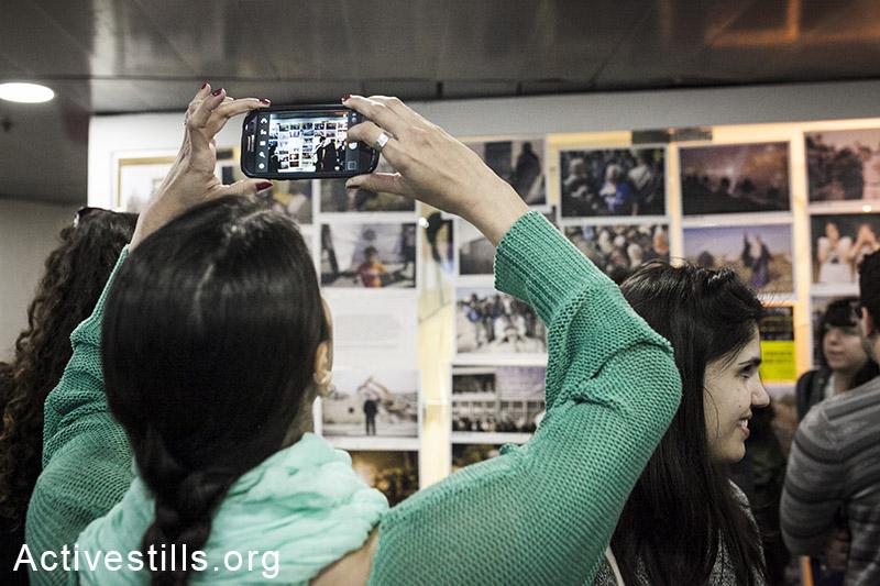 סטודנטים במכללת שנקר להנדסה ועיצוב מצלמים את תערוכת הצילומים של קולקטיב אקטיבסטילס במסגרת כנס ״תרבות חזותית בין ציות להתנגדות״, רמת גן, ישראל, ה-30 למרץ, 2014.