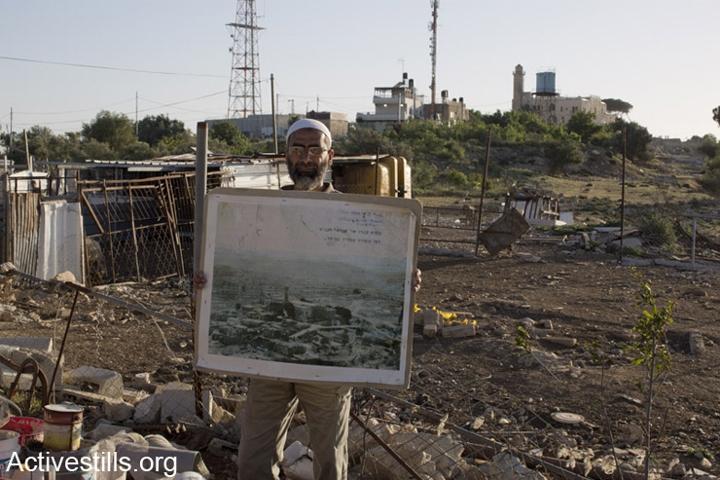 עיד ברקאת, תושב נבי סמואל, עומד מול המסגד עם תמונה של כפרו שנהרס כשהיה בן 7. צילום: מרייקה לאוקן וקרן מנור / אקטיבסטילס