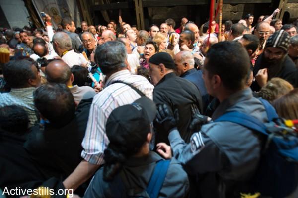 """שוטרים ישראלים דוחפים מתפללים בכנסיית הקבר בעיר העתיקה בירושלים, ה- 19 לאפריל 2014. יום לפני חג הפסחא, פלסטינים ותיירים נוצרים רבים משתתפים בחגיגות """"האש הקדושה"""" בכנסייה אשר בה, לפי האמונה, נצלב, נקבר וקם לתחייה ישו. בג""""צ קבע החודש כי ההגבלות שהמדינה מטילה על התנועה בין ישראל לשטחים פוגעות בחופש הדת. פלסטינים רבים התלוננו על יחס נוקשה מצד משטרת ישראל בזמן ניסיונותיהם להגיע להתפלל במקומות הקדושים. (אקטיבסטילס)"""