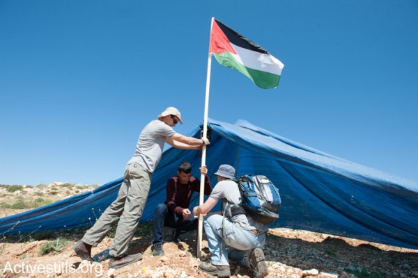 """פעילים פלסטינים וישראלים מציבים דגל פלסטין סמוך לאוהל שהוקם ע""""י מתנחלים על אדמה השייכת לכפר הפלסטיני חירבת א-נחלה, ה- 18 לאפריל, 2014. (אקטיבסטילס)"""