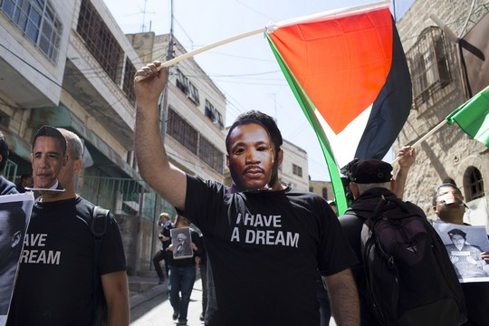 צעירים נגד התנחלויות ופעילים נוספים עוטים מסכות של מרטין לותר קינג ושל ברק אובמה בהפגנה בחברון בזמן ביקורו של הנשיא האמריקאי בישראל (צילום: אקטיבסטילס)