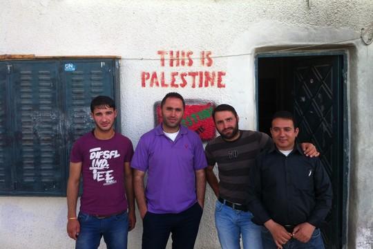 """עיסא עמרו (שני משמאל) ופעילים בכניסה למרכז """"צעירים נגד התנחלויות"""" (צילום: מוריאל רוטמן)"""