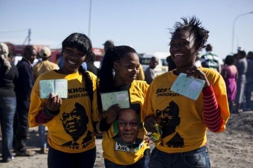 """קייפטאון. תומכות של מפלגת """"הקונגרס הלאומי האפריקאי"""" מציגות את תעודות הזהות שלהן. השלוש הן """"BORN FREE"""" ונולדו לאחר סיום שלטון האפרטהייד. זו מערכת הבחירות הראשונה בה הן מצביעות."""