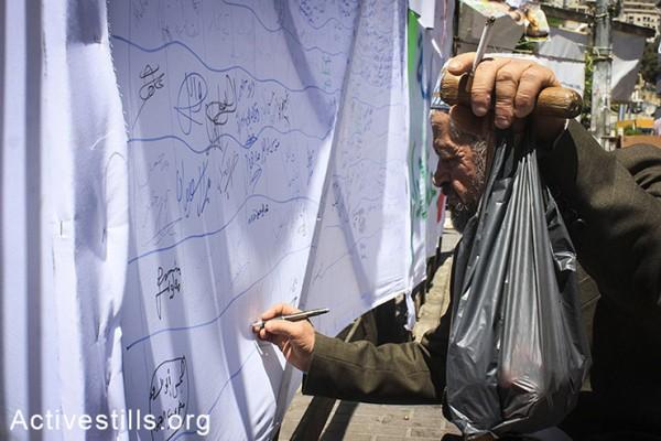 פלסטיני חותם על מכתב הזדהות אשר מיועד לעצירים מנהליים שובתי רעב בבתי כלא ישראליים, שכם, הגדה המערבית, ה-2 במאי, 2014. (אחמד אל-באז/אקטיבסטילס)
