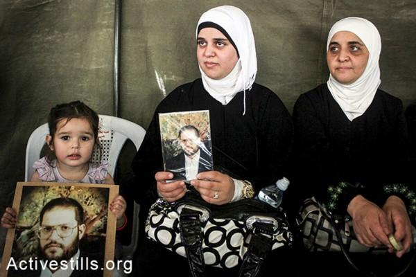 נשים פלסטיניות מחזיקות תמונות בסולדריות עם עצירים מנהליים השובתים רעב בבתי כלא ישראליים, שכם, הגדה המערבית, ה-2 במאי, 2014. (אחמד אל-באז/אקטיבסטילס)
