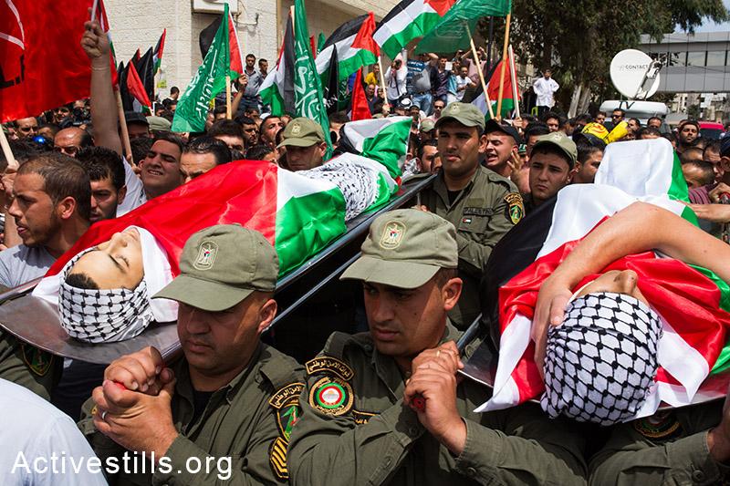 אנשי בטחון פלסטינים נושאים את גופותיהם של נאדים נווארה ומוחמד אבו-ט'אהר, שנהרגו בביתוניא, רמאללה, ה-16 למאי, 2014. (יותם רונן/אקטיבסטילס)