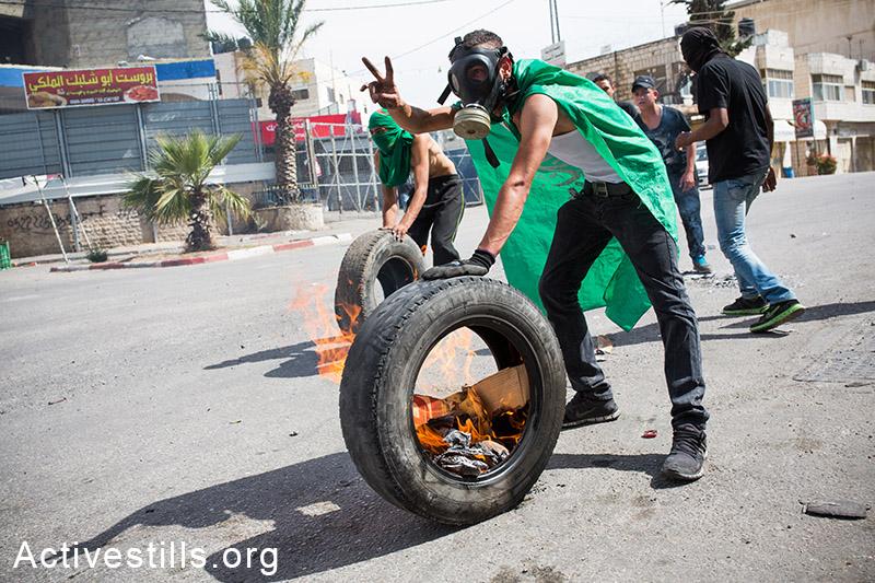 צעירים פלסטינים מתעמתים עם חיילים לאחר לוויות ההרוגים מאירועי יום הנכבה, ה-16 למאי, 2014. (יותם רונן/אקטיבסטילס)