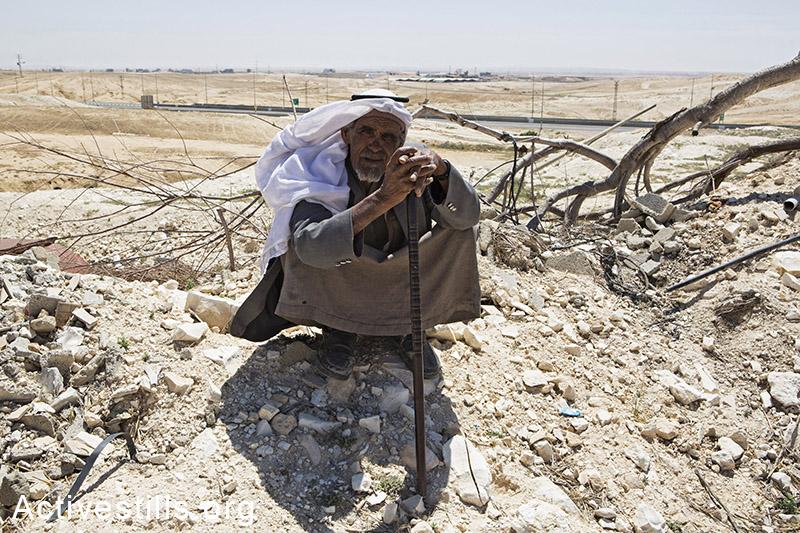 איש ממשפחת זאנון יושב על חורבות ביתו, דקות לאחר שרשות מקרקעי ישראל בגיבוי כוחות משטרה הרסו את הבית, ואדי אל-נעם, ה-18 במאי, 2014. (קרן מנור/אקטיבסטילס)