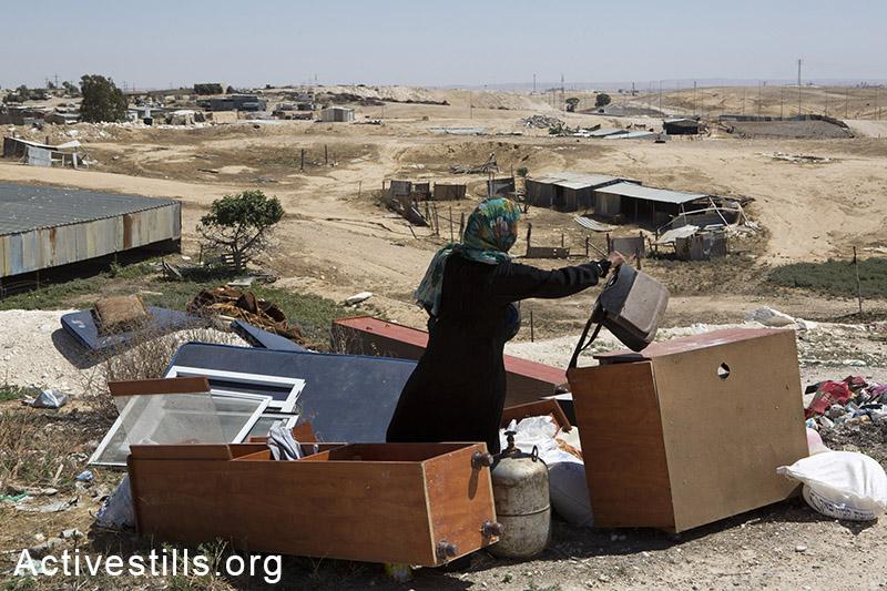 אישה ממשפחת זאנון מארגנת חפצים של המשפחה, דקות לאחר שרשות מקרקעי ישראל בגיבוי כוחות משטרה הרסו את ביתה, ואדי אל-נעם, ה-18 במאי, 2014. (קרן מנור/אקטיבסטילס)