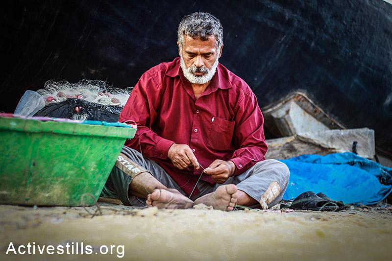 דייג מכין פתיונות למכירה, חוף עזה. (באזל יאזורי/אקטיבסטילס)