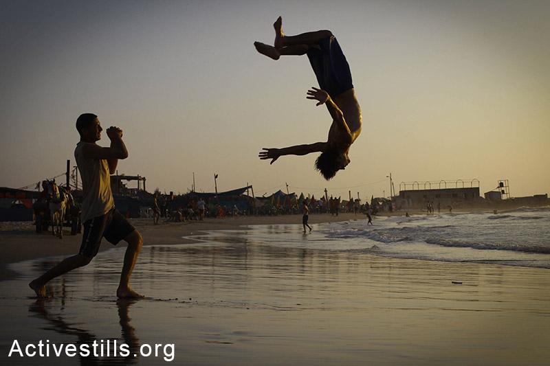 נערים מתאמנים באקרובטיקה על החוף, עזה. (באזל יאזורי/אקטיבסטילס)