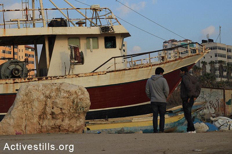 נערים צעירים עומדים ליד ספינה ישנה בנמל עזה. (באזל יאזורי/אקטיבסטילס)